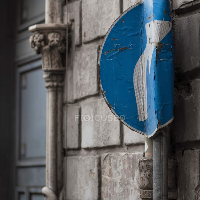 Smashed blue road sign with turn arrow — Stock Photo