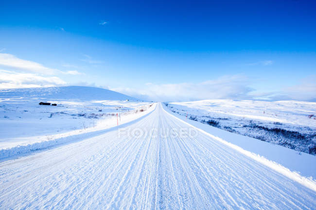 Snowy road in sunny daylight — Stock Photo