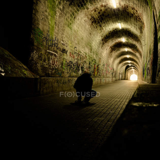 Urban scene, inner dark tunnel view and silhouette of sitting man — Stock Photo