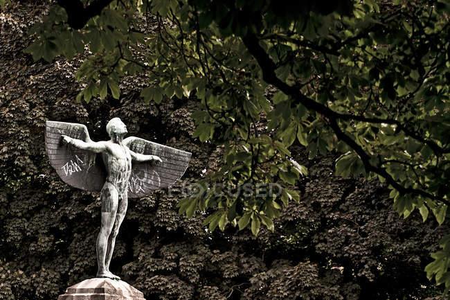 Vista diurna da estátua de homem com asas sob árvores — Fotografia de Stock