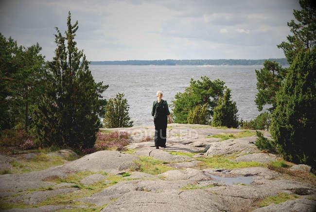 Donna di viaggiatore in piedi su una scogliera rocciosa a Lago — Foto stock