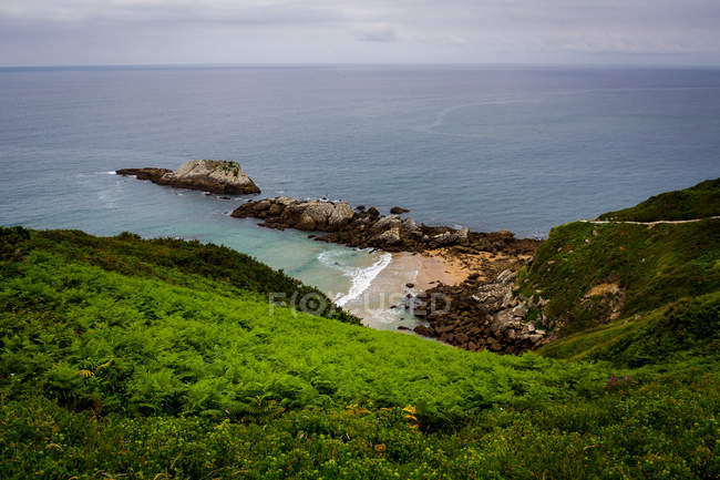 Seashore with green hills, rocks and  beach — Stock Photo