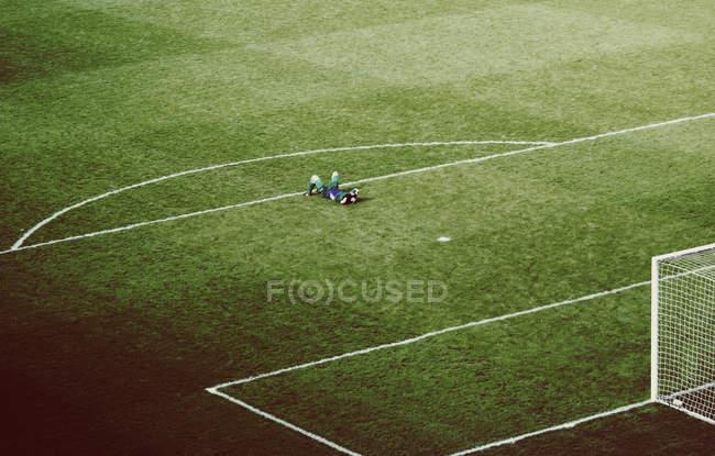 Vista elevada del suelo del estadio y jugador acostado sobre la hierba verde - foto de stock