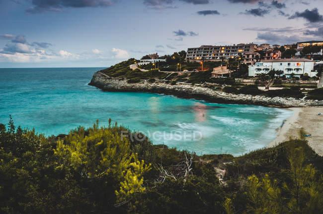 Прекрасный вид на остров с зданиями и бирюзовый океан воды — стоковое фото