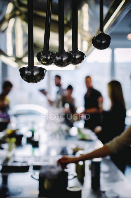 Hanging ladles in restaurant with set table and blurred people on background — Stock Photo