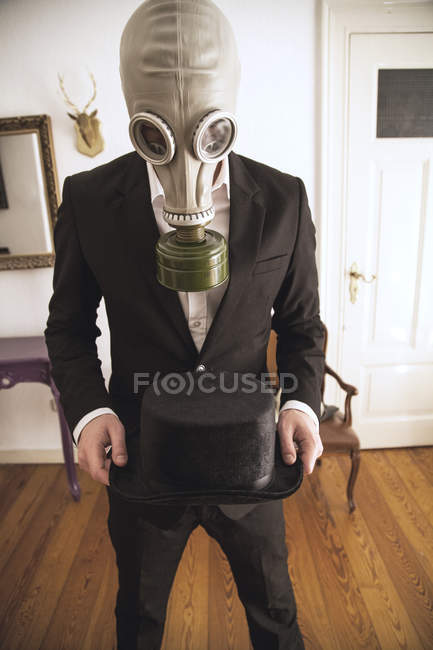 Cropped portrait of man in suit and gas mask holding black hat indoors — Stock Photo