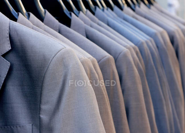 Row of suits hanging on rack in store — Stock Photo