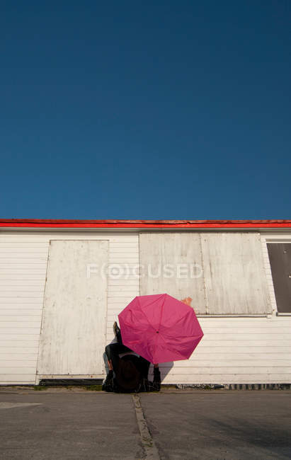 Colorful umbrella by the container in sunshine — Stock Photo