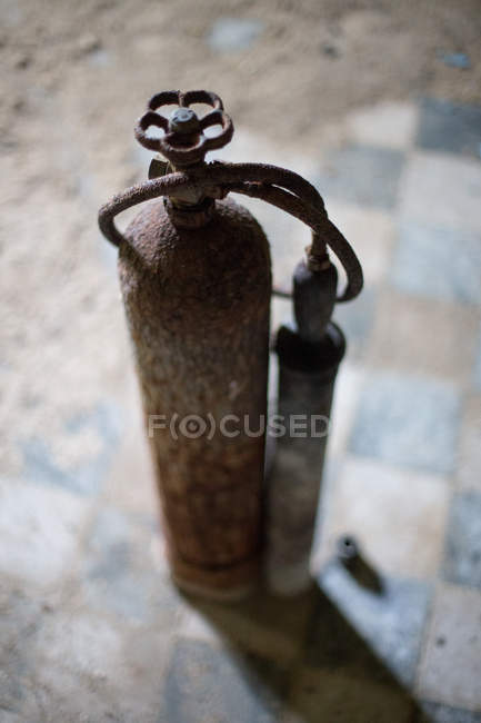 Daytime elevated view of rusty gas cylinders with hose — Stock Photo