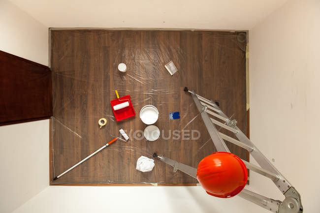 Top view of room decoration, ladder with safety helmet paint and brushes on wooden flooring — Stock Photo