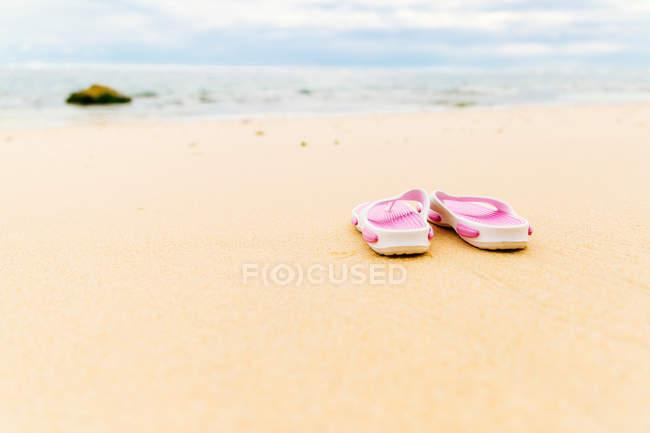Flip flops on sandy beach — Stock Photo