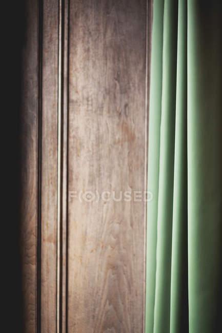 Vista diurna de la cortina verde y tubo de metal en madera de la pared - foto de stock