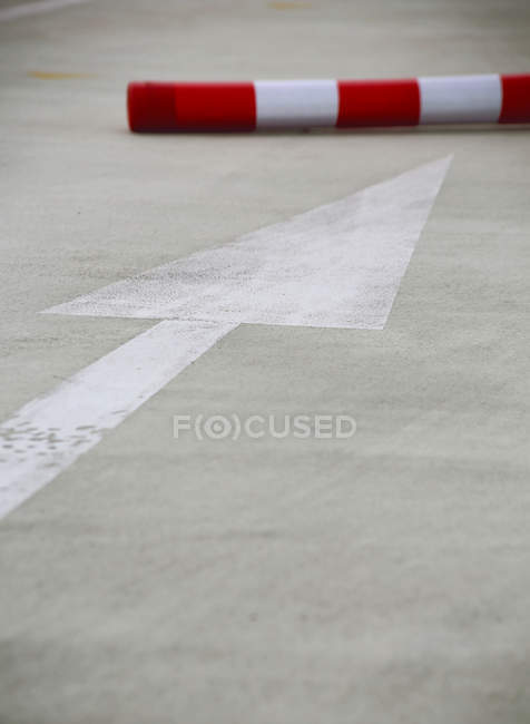 Asphalt road with arrow sign and red tube — Stock Photo