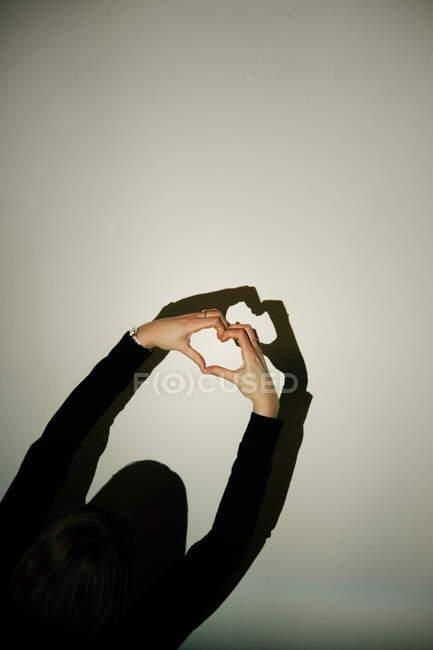 Femme gesticulant en forme de cœur avec les doigts au mur avec une ombre — Photo de stock
