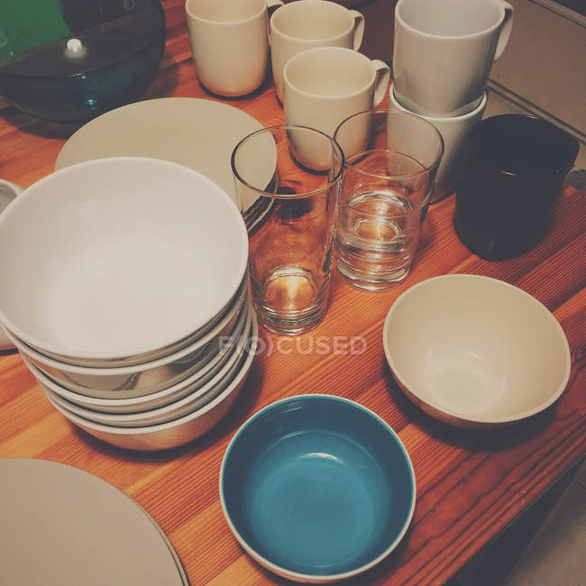 Cropped view of clean crockery and glasses on kitchen table — Stock Photo