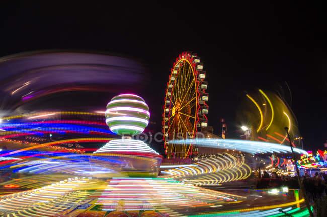 Bewegung Blick auf erleichterte Bewegung schwingen und Riesenrad am Abend — Stockfoto