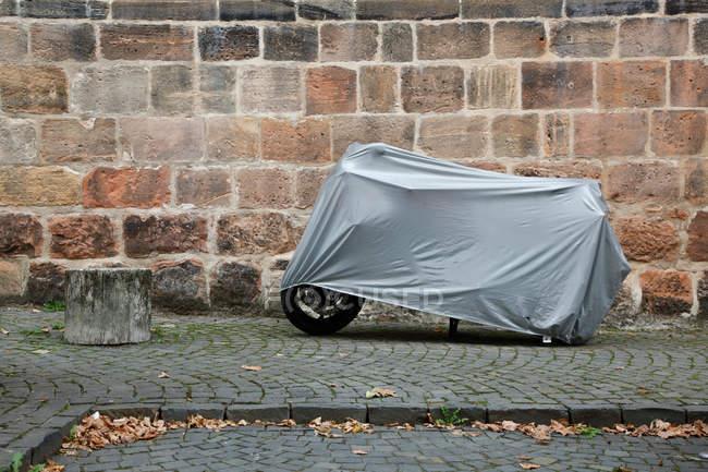 Дневной вид мотоцикл в серый чехол припаркованные возле кирпичной стены на асфальте — стоковое фото
