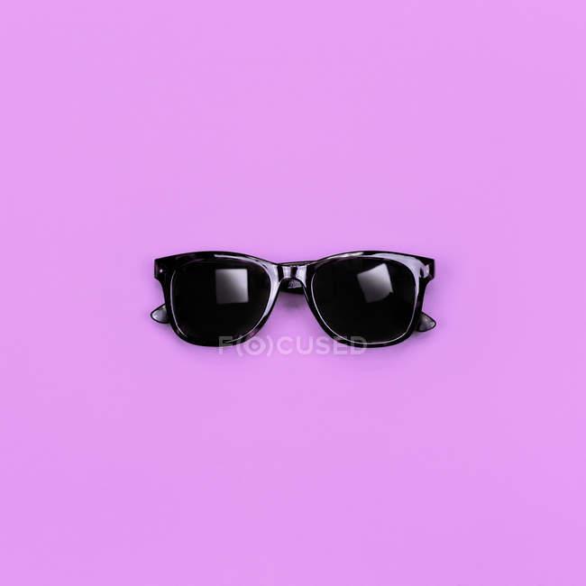 Black stylish hipster sunglasses on purple surface — Stock Photo
