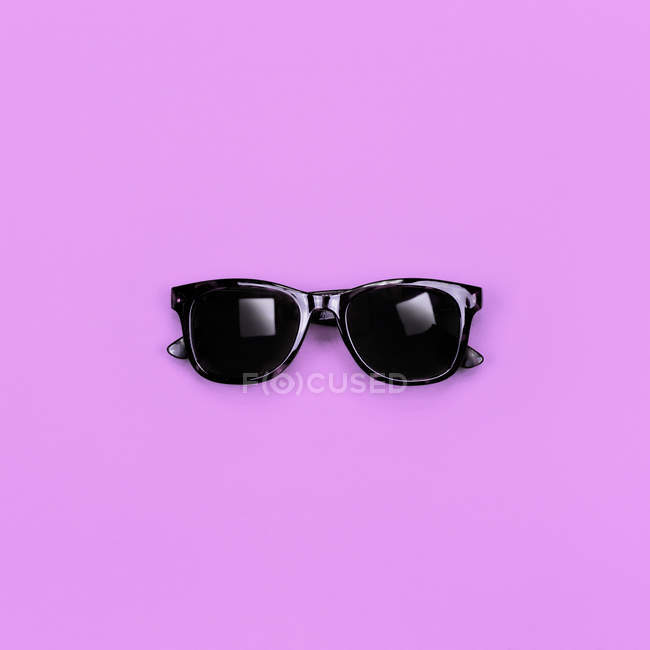 Black stylish hipster sunglasses on purple surface — Stock Photo