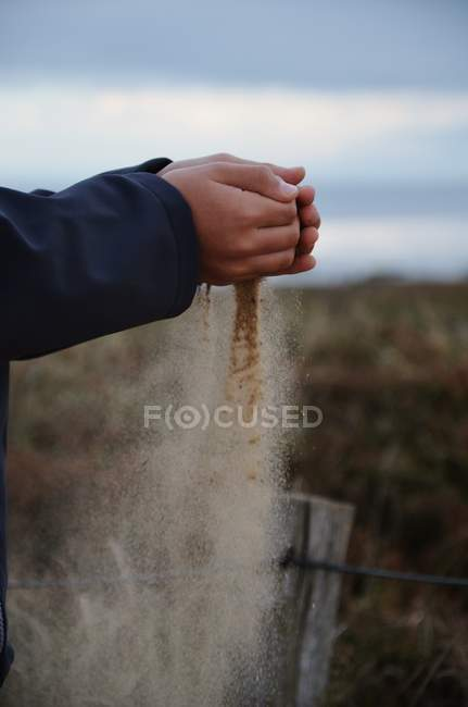Close-up view of hands holding sand — Stock Photo