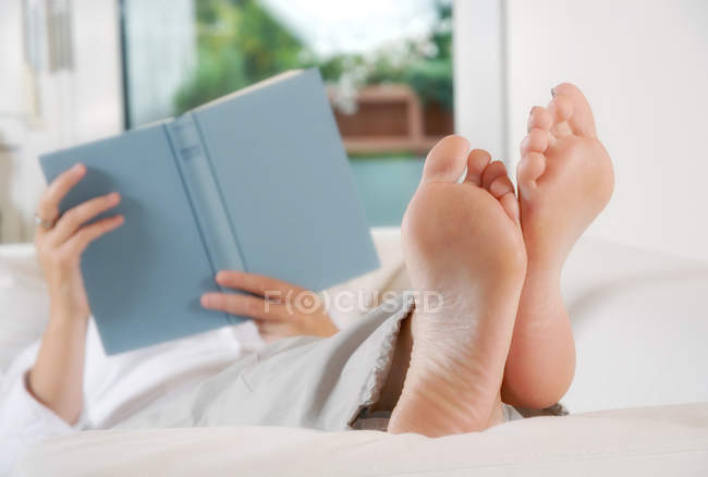 Woman lying on couch reading book — Stock Photo