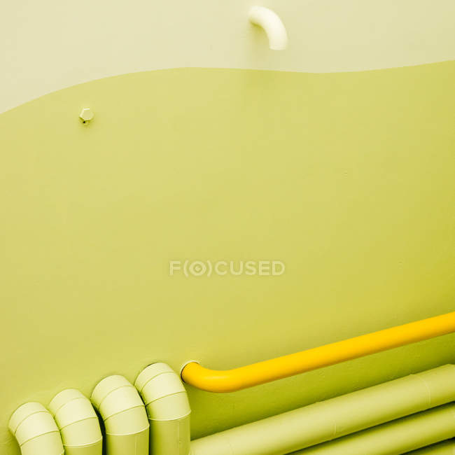 Full frame image of yellow lime color wall and iron tubes — Stock ...