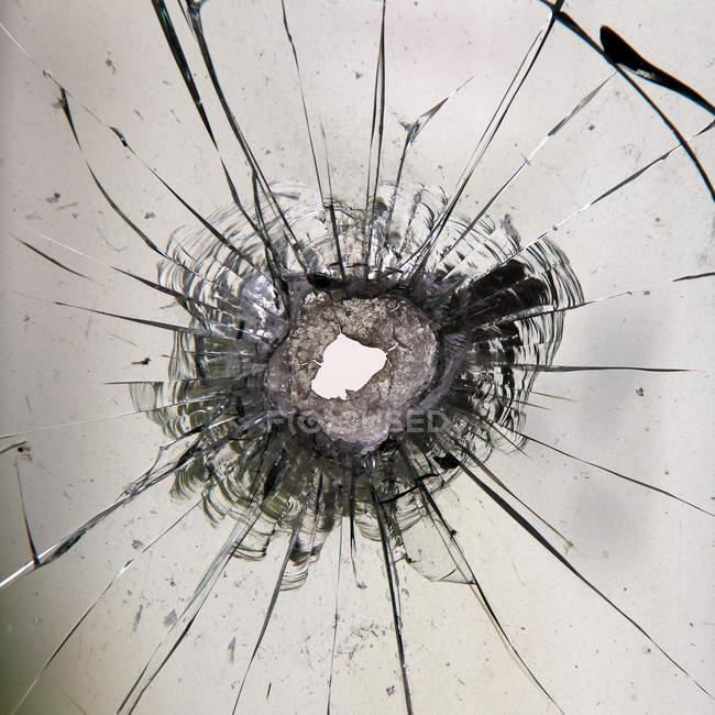Window pane with hole of gun bullet — Stock Photo