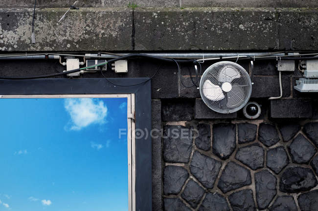 Daytime view of fan with camera, lantern and wires on stone wall over poster with sky image — Stock Photo