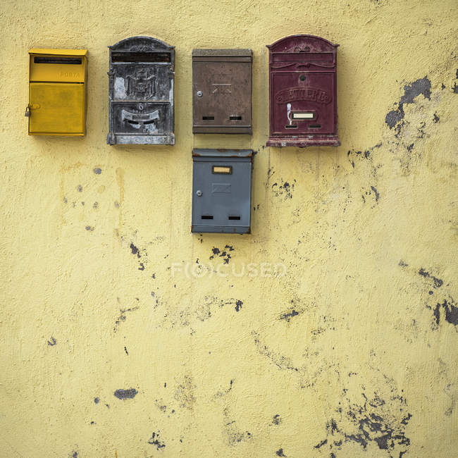 Aged yellow wall with mail boxes — Stock Photo