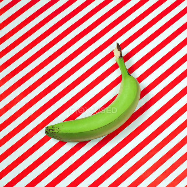 Green banana on striped surface — Stock Photo