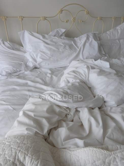 Comfortable light bedroom with crumpled bedding — Stock Photo