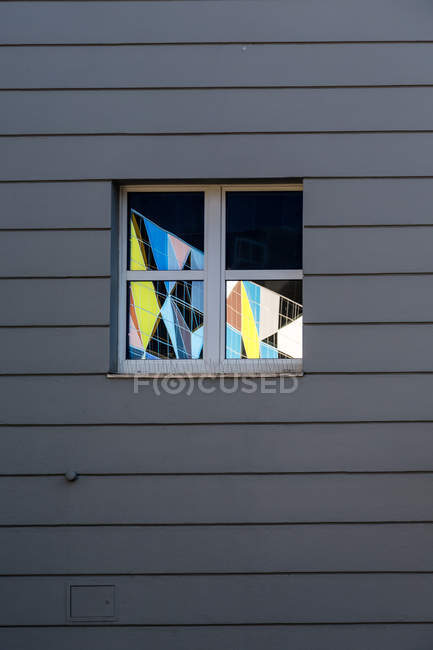 Colorful tile pattern reflecting in window at grey wooden wall — Stock Photo