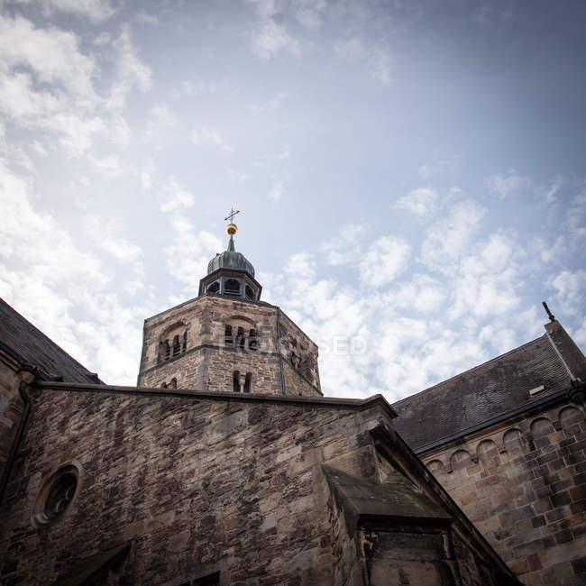 Живописный вид на крыши церкви с крест под пасмурным небом — стоковое фото