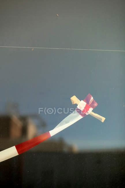 Fita vermelha e branca, fixada no painel de vidro com fita adesiva — Fotografia de Stock