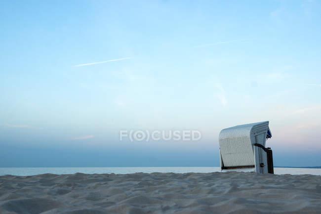 Tumbona en la playa de arena junto al mar - foto de stock