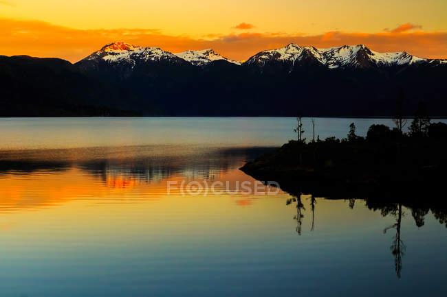 Bela vista panorâmica do Lago contra a neve cobriu picos de montanha no pôr do sol — Fotografia de Stock
