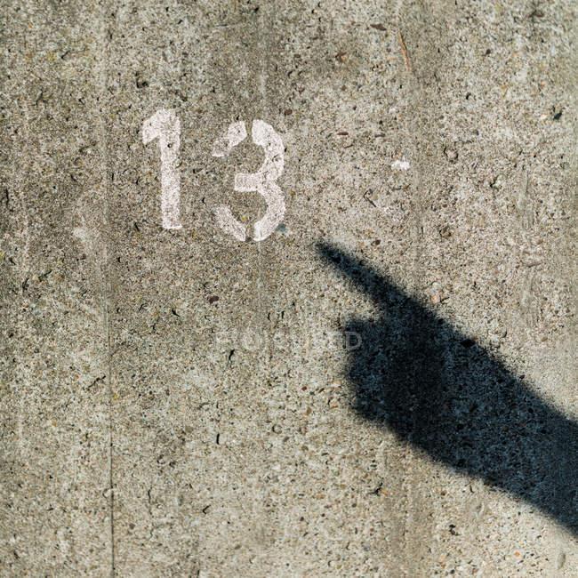 Крупным планом вид тени руку, указывая на номер — стоковое фото