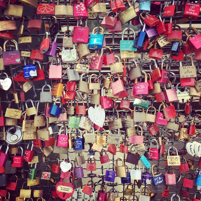 Cadenas d'amour, nombreuses serrures différentes suspendus — Photo de stock