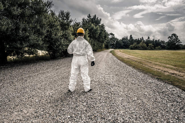 Rear view of man in protective workwear and helmet on asphalt road by the field — Stock Photo