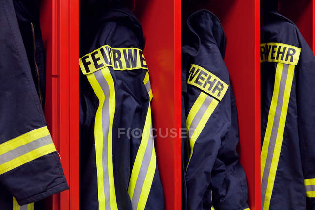 Closeup view of firefighters protective clothing in red wardrobe — Stock Photo