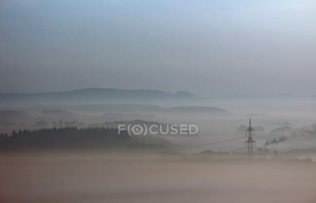 Natural landscape and power lines view in foggy weather — Stock Photo