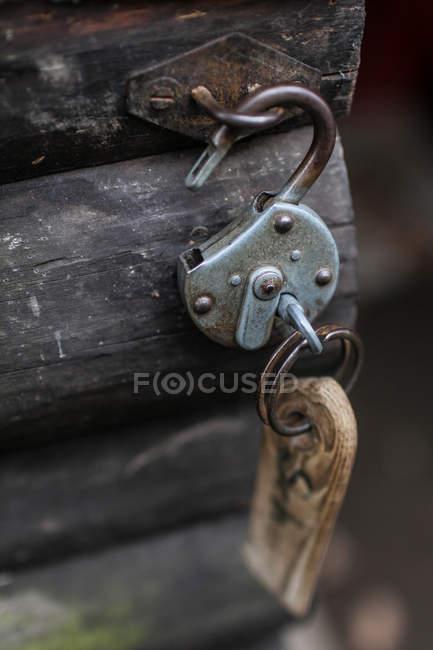 Opened rusty padlock hanging on wooden door — Stock Photo