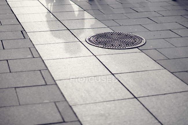 Дневной вид плиточные покрытия с канализационный люк и людские тени — стоковое фото