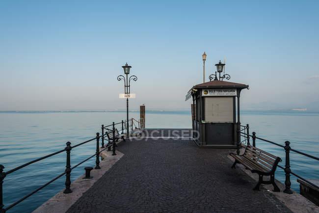 Muelle de mar con linternas y puesto al atardecer - foto de stock