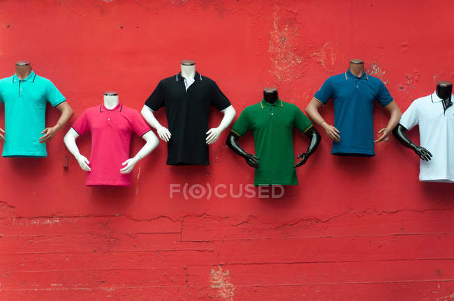 Mannequins in t-shirts hanging on red brick wall — Stock Photo