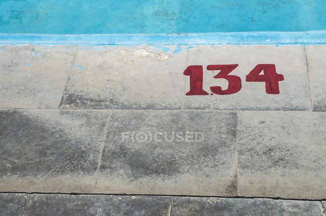 Vista do close-up de número em pedras de pavimentação — Fotografia de Stock