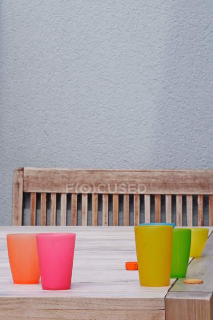 Bunte Plastikbecher auf Tisch — Stockfoto