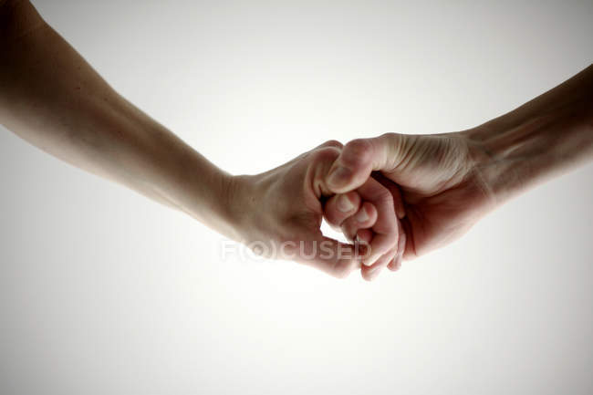 Cropped view of male and female hands holding each other on white background — Stock Photo