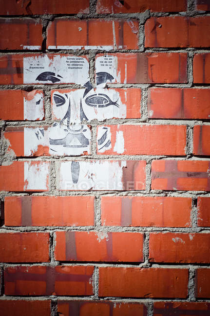 Close-up of shabby poster on brick wall — Stock Photo