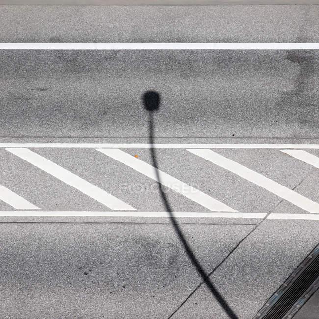 Strada di asfalto grigio con linee bianche e lampada di via ombra — Foto stock